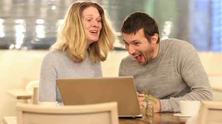 gritar : Front view of excited couple cheking laptop content sitting in a coffee shop in the Vídeos