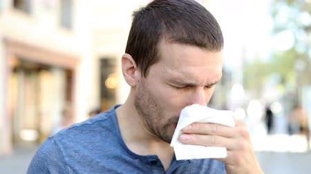 epidemy : Portrait of an adult ill man sneezing using a tissue standing in the street Stock Footage
