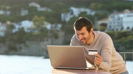 barganha : Excited man paying with laptop and credit card in a balcony on the beach on vacation