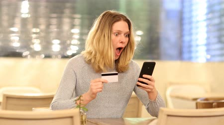 alku : Excited woman buying online in a bar in the night with credit card and smart phone Stock mozgókép