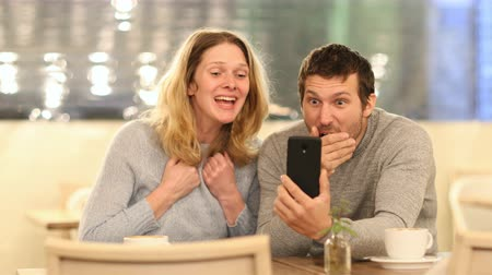 you win : Excited couple reading good news on mobile phone sitting in a coffee shop in the night Stock Footage