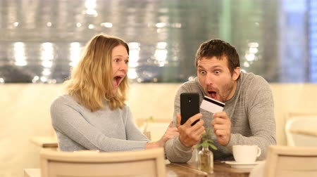 торг : Excited couple finding offers buying online in a bar in the night with mobile phone and credit
