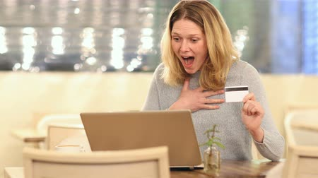 barganha : Excited woman buying online in a coffee shop with a laptop and credit card