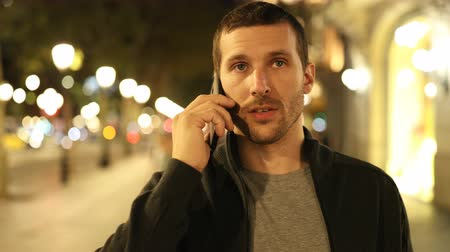 Front view of a serious man walking talking on phone in the night in the street