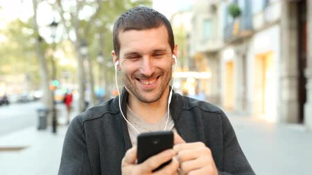 learning to walk : Front view of a happy man listening to music checking mobile phone at evening walking Stock Footage