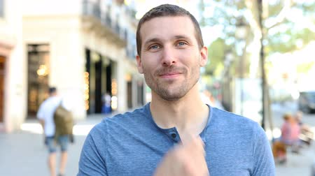 Front view portrait of a happy adult man looking at camera in the street