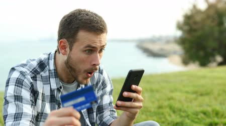 потребитель : Surprised man paying with credit card and mobile phone sitting on the grass