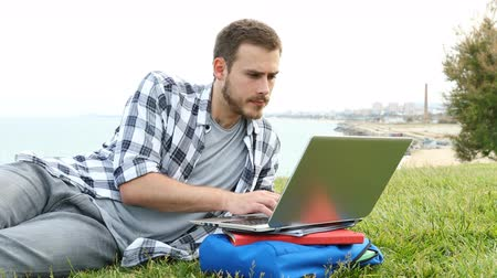 külvárosok : Serious student e-learning using a laptop lying on the grass