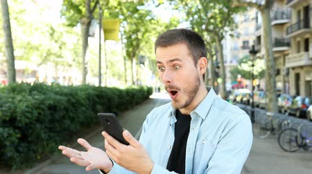 Surprised man using a mobile phone finds amazing content and looks at camera in the