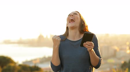 торг : Front view portrait of an excited woman checking mobile phone celebrating success in a