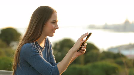 Profile of a serious girl using mobile phone in a park