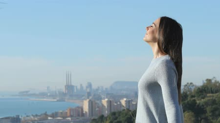 Profile of a relaxed woman breathing deeply fresh air in a city outskirts Dostupné videozáznamy