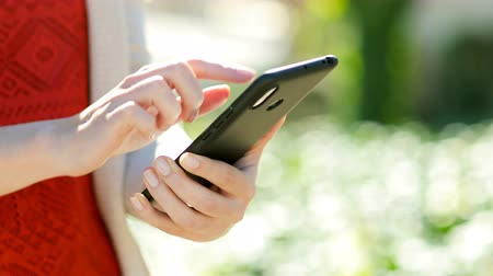 download : Close up of a woman hand using mobile phone in a park with a warm light Vídeos