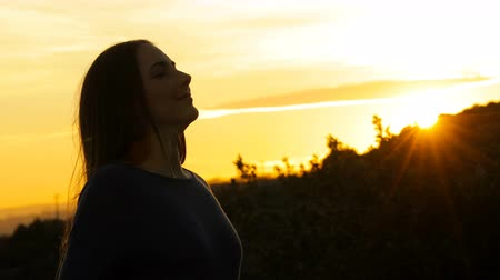 Silhouette of a woman breathing fresh air at sunset in the mountain Stockvideo