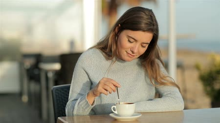 vendég : Happy girl stirring coffe sitting in a restaurant in slow motion