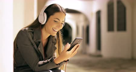 Happy girl listening to music from smart phone sitting in the street in the night