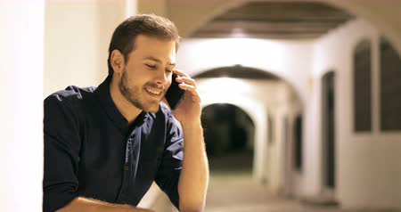 tebliğ : Happy man talking on mobile phone sitting in the street in the night
