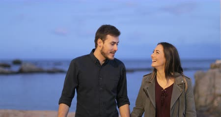 bem estar : Front view of a happy couple walking talking in a first date on the beach at evening Stock Footage