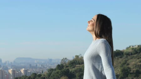 Side view portrait of a relaxed woman breathing fresh air far from city