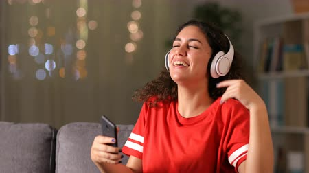 Happy arab girl dancing and listening to music with smart phone and headphones at home in the night