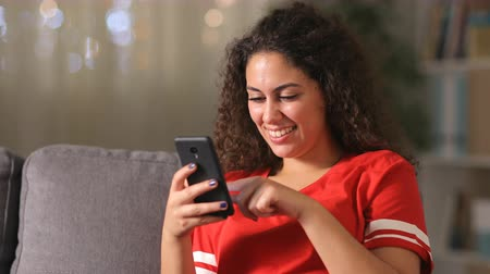 Happy arab girl in red using smart phone sitting on a couch at home in the night