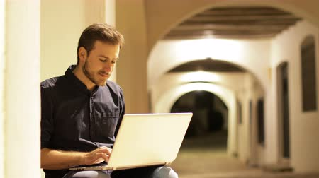 Man typing on laptop and looking at camera smiling in the street in the night