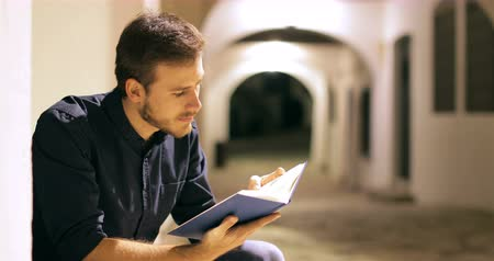 esteem : Happy man reading a paper book sitting in the street in the night Stock Footage