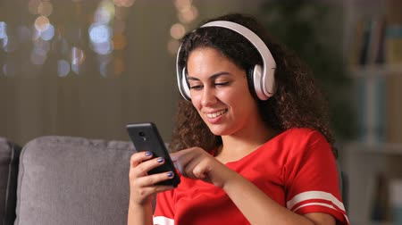 download : Happy arab girl wearing wireless headphones listening to music checking phone at home