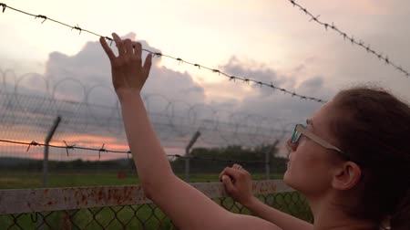 göçmen : the girl tries to climb on a fence of barbed wire and is punctured