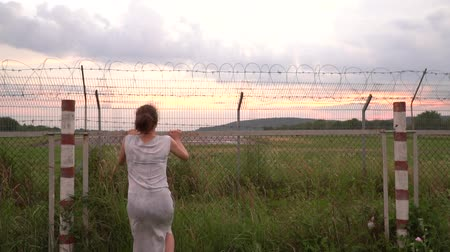 oszlopsor : the girl tries to climb over the fence with barbed wire