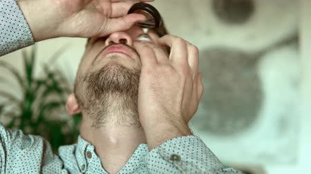 успокаивающий : Guy administers eye drops to alleviate irritated dry eye. Water drop makes contact with surface of amber colored eye. Стоковые видеозаписи