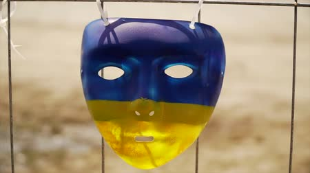 ocupação profissional : blue-yellow mask hanging on the fence and staggering in the wind Stock Footage