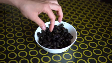 dut : Mulberry on the bowl. a man takes a mulberry in a bowl