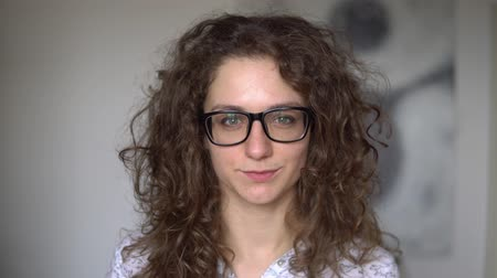 ношение : curly-haired girl wears black glasses, smiles and laughs.close up. against the white room. Skyes wearing a white shirt.