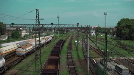 sleepers : railway tracks, freight train with empty cars, the camera turns, in the background of other trains and the railway goes away, there are electric poles and hanging wires. Tanks and locomotives