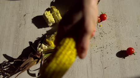 eaten : two hands trying to take one corn cob and begin to take it from each other. against cherry tomatoes and empty ears of corn
