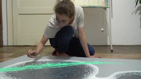 tanımlayıcı : the artist sits on the floor and draw a big picture with a brush. draw on a gray picture of green stains.