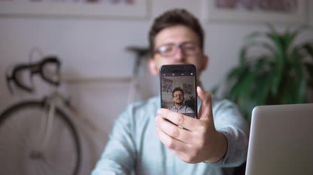 tárcsázás : a young guy takes a selfie, sitting at the laptop against the wall with a bike. a young businessman at a laptop makes a selfie. close up. against the bike. in the blue shirt. and black glasses.