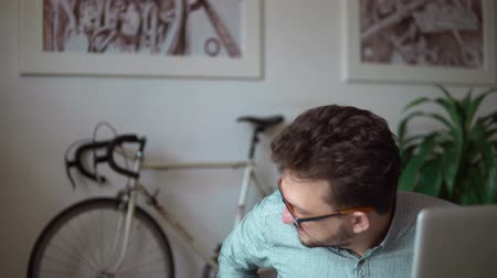 tárcsázás : a young businessman sitting at a laptop working. then they look at the phone for a while. rejoice and turns around gets up takes the bike and leaves. against the white wall, flower, bike. Stock mozgókép