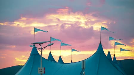marquee : In the wind fluttering flags on the circus tent against the beautiful evening sky at sunset Stock Footage