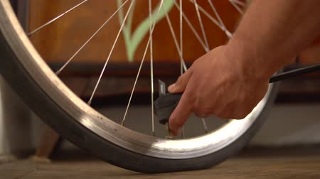 ar : Inflate the tire of the bike. Remove the lid from the Bicycle wheel, lifts the valve and puts the pump on it. pumps the wheel, removes the pump and closes the lid. Stock Footage