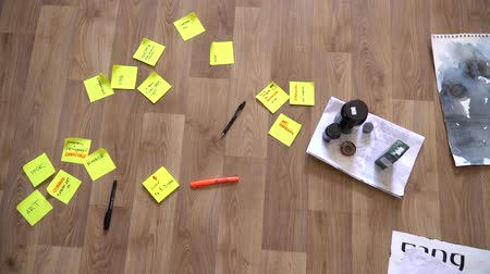 On the wooden floor are stickers, pens, books. Close up. working environment Stock Footage
