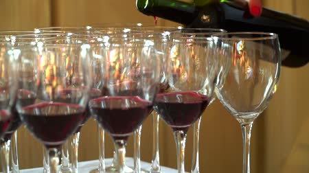 официант : The waiter pours red wine in the rows of glasses.On the table is a bunch of red glasses. Wine tasting.