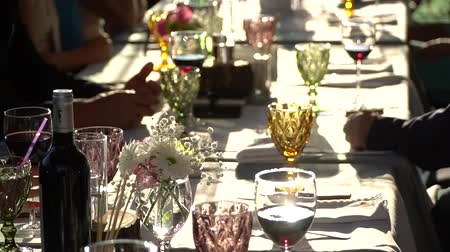 People at the table tasting wine. Clink glasses of red wine. On the table white tablecloth and utensils. Wine tasting. Stock Footage