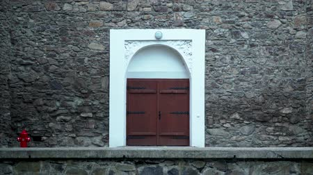 Wooden door of an old stone building. brown wooden, double door with white stone wall edging. Stock Footage
