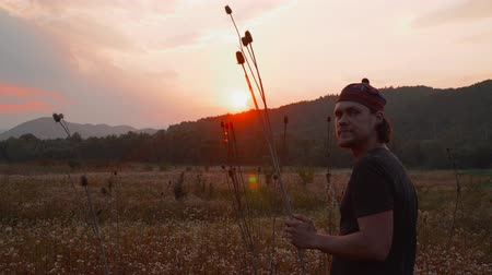The guy is standing in the field at sunset and holding a thorn. in the background you can see the forest and mountains. Beautiful summer sunset.