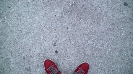 The guy is standing in red sneakers on the concrete. All you can see is the sneakers and the gravel. Red sneakers are laced with white laces.