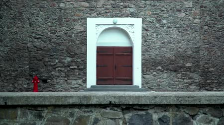 Wooden door of an old stone building. brown wooden, double door with white stone wall edging. Stok Video