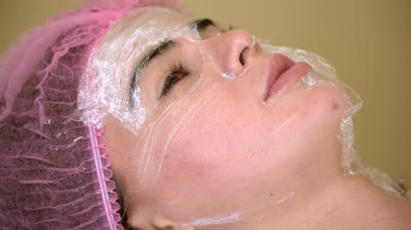 the doctor wipes the mask from the patient. plastic surgery. girl at the Spa. the mask on the face.