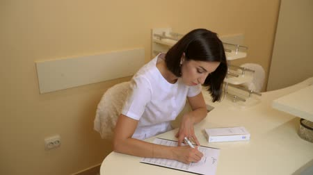 the doctor sits at the table and writes something. plastic surgeon in white robe sitting at the table and writing on paper. in the office. girl. Stock Footage